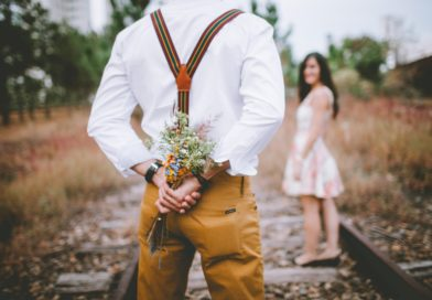 Man with bouquet in hands behind his back in front of woman