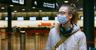 A female traveler wears a mask in an airport.