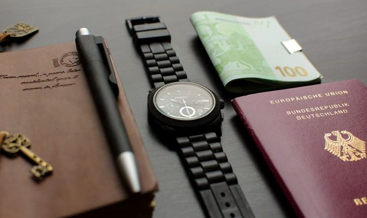 A passport, watch, and money on a table